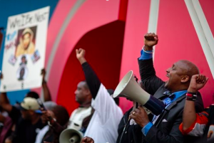 Attorney Mawuli Mel Davis, Partner Davis Bozeman Law Firm, chants during a protest downtown of George Zimmerman's not guilty verdict in the 2012 shooting death of teenager Trayvon Martin, Monday, July 15, 2013, in Atlanta (Associated Press Photo/David Goldman)